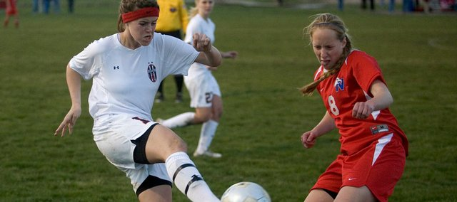 Lawrence High's Kaley Tesdahl, left, plays a ball in front of Olathe North's Kristy Carter. LHS shut out Olathe North, 1-0, on Tuesday at Youth Sports Inc.