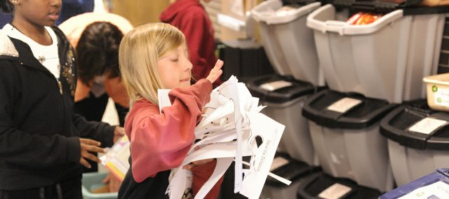 Rhiannon Emerson, 10, looks for the right bin while sorting materials for recycling at Broken Arrow School, 2704 La.