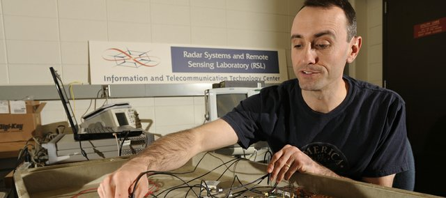 Geoff Akers, doctoral student at Kansas University, works in the Remote Sensing Lab at Nichols Hall. Tom Kern, Lawrence Chamber of Commerce president and CEO, notes that KU's research can be a boon for Lawrence's economy.