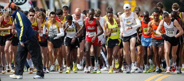 The race starter walks off the course as the elite men runners take their first step off the starting line of the 113th Boston Marathon in Hopkington, Mass. Ethiopia's Deriba Merga won the men's race, Kenya's Salina Kosgei won the women's race, and Americans placed third in each race.