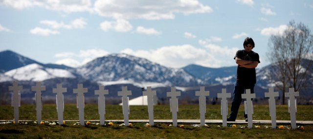 "Garrett Bentley looks at a display of crosses for the 13 victims of the massacre at Columbine High School to mark the 10th anniversary of the killings Monday near the Columbine Memorial in the southwest Denver suburb of Littleton, Colo. About 1,000 people gathered for a sunset memorial service at Clement Park, next to the school, where survivors, relatives and current students reflected on the massacre. A dove was released for each of the 13 victims as Principal Frank DeAngelis read their names. Addressing the survivors, DeAngelis said: ""You were forced to grow up far too quickly."""