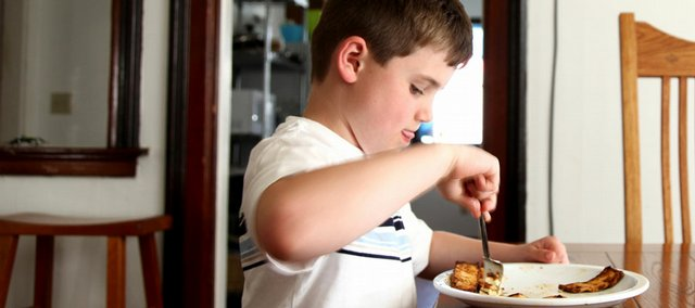 Nathan Williams, of Lawrence, digs into a plate of tofu marinated in tomato and garlic after school. The Cordley School student won the Sunflower State Games Essay Contest in 2009 about healthy eating.