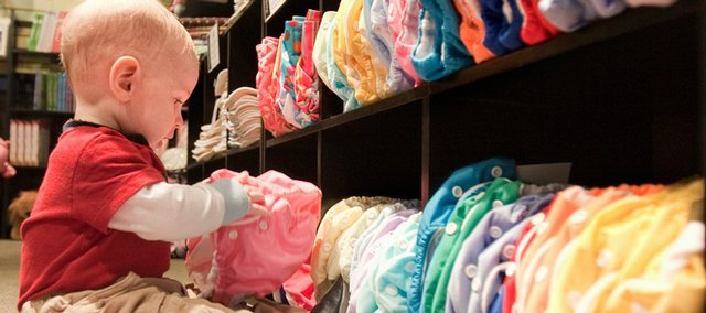 Eight-month-old Ezra Bird occupies himself with cloth diapers at the Circle Me store in Lincoln, Neb., in this Feb. 5 photo. With the economy in a downward spiral, some parents are turning to reusable cloth diapers for their kids.