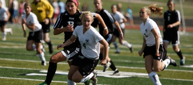 Free State sophomore forward Amanda Moyer chases down a loose ball with Shawnee Mission East sophomore midfielder Kirsten Clark during the first half Tuesday, April 21, 2009 at Free State High School.