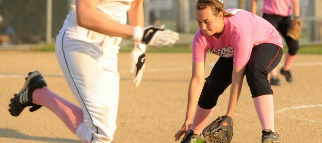 LHS pitcher Lauren Massey picks up a ground ball by Shawnee Mission South's Heather Lauret Tuesday evening at Holcom Sports Complex.