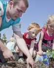 Volunteer Connor Donevan, a Kansas University senior, helped preschoolers Chandler McDuffy, 4, center, and Chloe Weins, 4, with the annual planting of a rain garden to celebrate Earth Day on Wednesday. The garden is in front of the Ambler Student Recreation Center at KU.