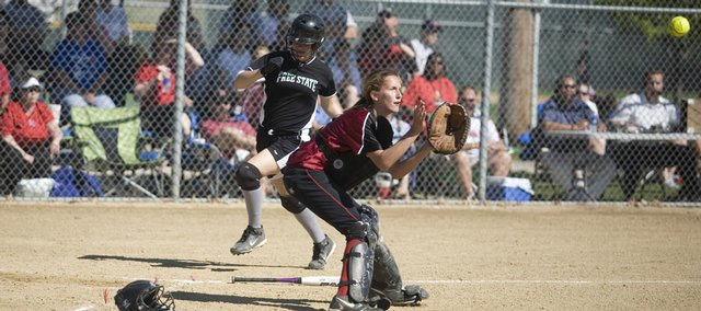 Lawrence High catcher Kristen Bell, right, gets ready to protect the plate as a Free State baserunner tries to score. The Firebirds swept the Lions, 7-2 and 7-3, on Thursday at Holcom Complex.