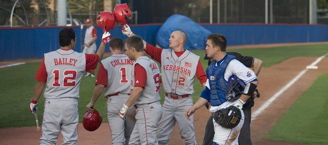 Kansas catcher Buck Afenir heads back behind the plate while Nebraska's Jake Mort (2) celebrates with teammates after his three-run home run in the fourth inning. The Huskers scored six runs in the inning and went on to win, 11-4, Friday at Hoglund Ballpark.
