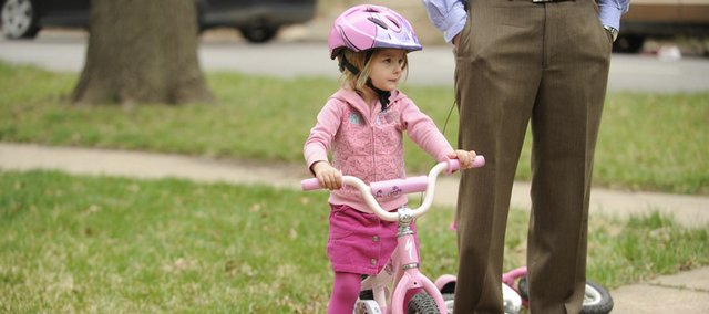 Kennedy Lamer, 3, of Lawrence, is learning how to ride her new bike with the help of parents Stacey and Chad.