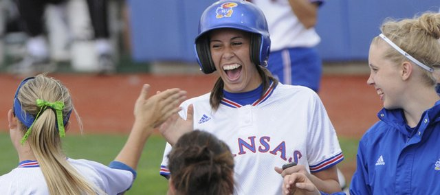 Allie Clark, center, celebrates with her teammates after hitting a two-run home-run in the bottom of the fifth inning in KU's 7-3 win over Baylor in the first game of a double-header Saturday at KU.