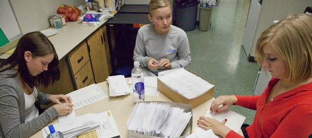 Free State High School students Ali Rueschoff, left, Kylie Wampler and Danielle Augustine address prom invitation envelopes in preparation for the annual party.