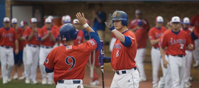 Kansas' Brian Heere (9) high-fives Tony Thompson after scoring a run that gave Kansas a 4-0 lead over Nebraska in the bottom of the third inning of the first game of a doubleheader. KU swept the Huskers on Sunday at Hoglund Ballpark.