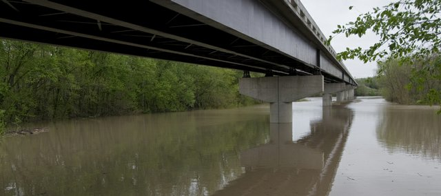 The Kansas River at the Lecompton Bridge spreads out beneath the bridge well beyond the banks of the river Monday. The National Weather Service in Topeka issued a flood warning for the Kansas River at Lecompton Monday. The warning is effect until Tuesday evening.