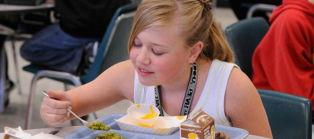 Morgan Davidson, 11, eats some peas as part of her school lunch at Prairie Park School. School district officials have tried over the past few years to improve the nutrition value of the meals that are served to students.