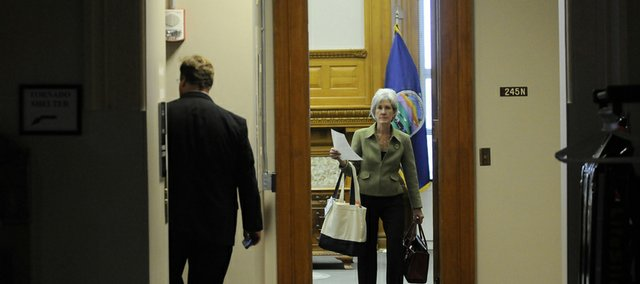 Gov. Kathleen Sebelius leaves her office with a security officer Tuesday at the Kansas Statehouse. She was confirmed as Secretary of Health and Human Services and will likely resign her post as governor.