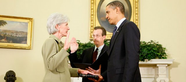 Health and Human Services Secretary Kathleen Sebelius is sworn in by Tim Saunders, Executive Clerk of the White House, as President Barack Obama holds the Bible on Tuesday in the Oval Office of the White House in Washington.