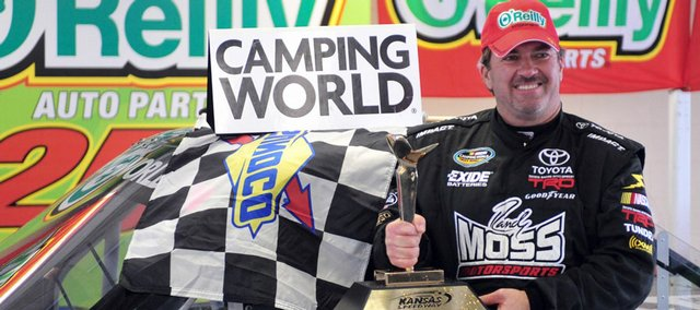 driver Mike Skinner poses with the trophy after winning the weather-shortened race Monday at Kansas Speedway.