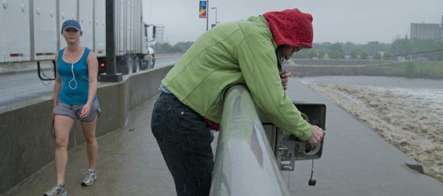 Kate Dinneen, duty officer with Douglas County Emergency Management, drops a weighted line to the surface of the Kansas River to measure the water's level Wednesday at noon. The county is tracking the river's level as additional rain fell on Lawrence Wednesday on top of ground already saturated from the weekend storms.