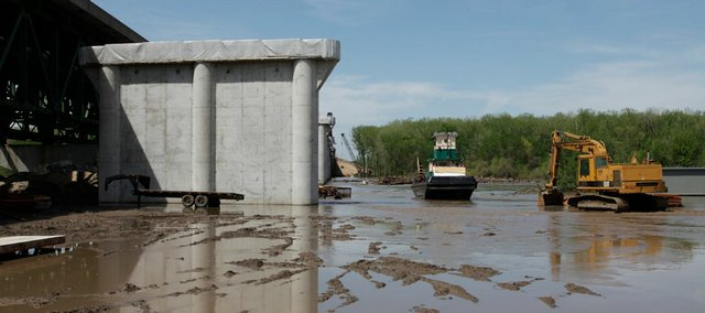 Heavy rains provoked rising waters on the Kansas River, flooding the construction site of the I-70 bridge and delaying the project's progress.