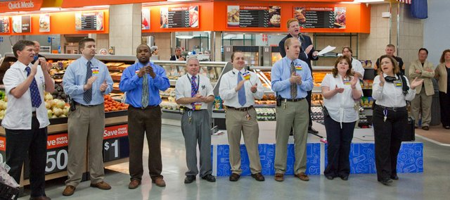 "Wal-Mart employees lead a group of associates in reciting the ""Wal-Mart cheer"" during the grand opening of the new store Wednesday morning."