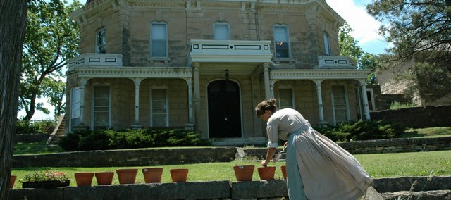 Heather Brown, park ranger at the Tallgrass Prairie National Preserve, pots some flowers in front of the park's 1883 Spring Hill farm ranch house. The house is part of the self-guided walking tour at the park.
