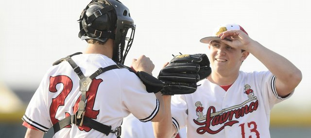 Lawrence High pitcher Albert Minnis gets some encouragement from catcher Jake Green during the fourth inning against Olathe East. Minnis struck out 14 in the Lions' 1-0 victory Friday at Free State High.