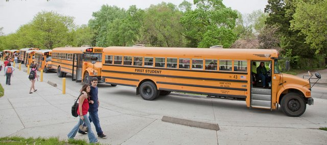 Lawrence High School Students board buses Tuesday afternoon as lawmakers discussed the state budget at the Capitol in Topeka. The 2.75 percent across-the-board cut that was approved by the Senate would trim funding to public schools by about $83 million.