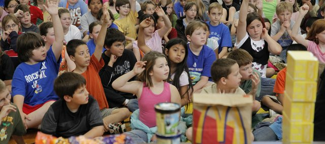 Students at Schwegler School try to answer questions about healthy eating during a lesson offered Thursday by nutrition educators from The Community Mercantile Co-op, 901 Iowa.
