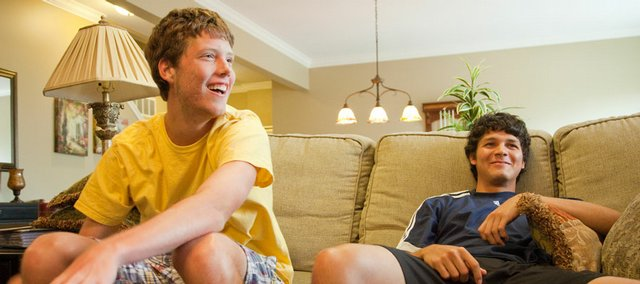 Michael Swank, left, and Rodolfo Gauto Mariotti compete in a FIFA 2009 soccer video game at Swank's house on Tuesday. Gauto Mariotti, a foreign exchange student, lives with Swank's family. The Free State tennis teammates will begin the Class 6A regional tournament today in Olathe.