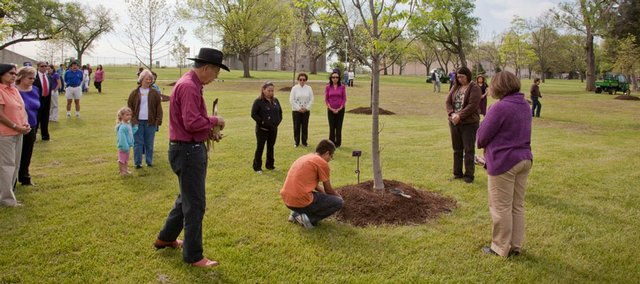 Members of the Haskell Indian Nations University community participate in a tree-blessing ceremony Wednesday at the campus. Elder Benny Smith, in black hat, conducted the ceremony.