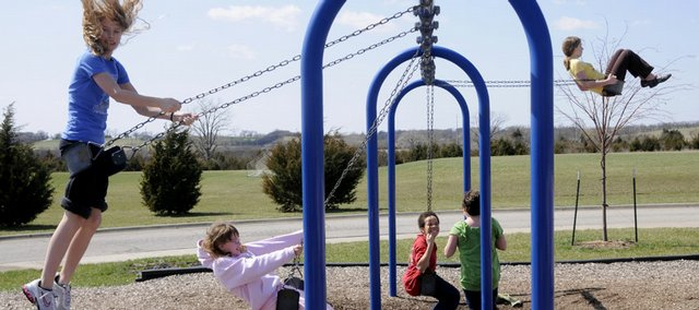 Students enjoy the ever-popular playground swings during recess at a Lawrence school.