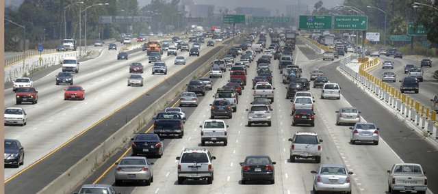 Traffic stacks up on the eastbound Santa Monica Freeway in Los Angeles, as residents leave work to start their holiday weekend in this July 3, 2008, file photo. The number of vacationing Americans will be down this summer, according to a new AP-Gfk Poll.
