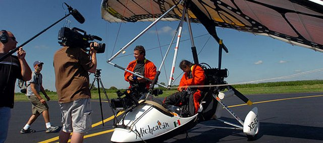 A documentary film crew surrounds pilots Vico Gutierrez and Tania Guerrero Collazo at Lawrence Municipal Airport in September 2005 as the two exit their ultralight plane, which is decorated as a Monarch butterfly. The crew stopped in Lawrence during their journey of following the migration of the butterfly from southeastern Canada to central Mexico.