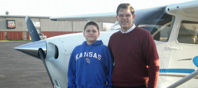 Nathan Patterson, 12, and his dad, Bob Patterson, visit Lawrence Municipal Airport for information on how young Nathan could fulfill his dream of becoming a pilot.