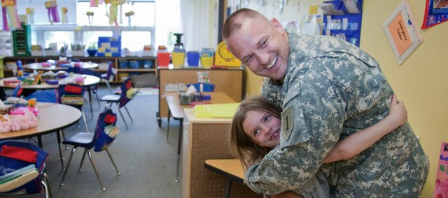 Langston Hughes first-grader Jaida Hammond hugs her dad, Eric Hammond, a chief warrant officer in the U.S. Army, on Wednesday in Leslie Ross' classroom at the school. Hammond, who has been serving in Iraq, is home for 15 days of leave and surprised his daughter with a visit to her classroom.