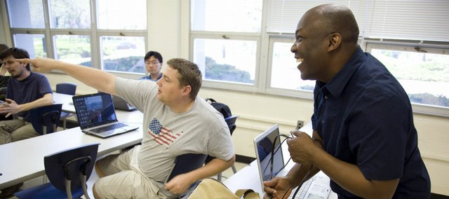 Kansas University graduate student Ari Jean-Baptiste, right, a chief warrant officer in the U.S. Army, laughs with classmate Matt Miles, a first-year graduate student from Lecompton, as he unloads his laptop in preparation for a statistics class recently at KU. During his second tour in Iraq, Jean-Baptiste sustained injuries when his helicopter went down near Kirkuk. That was in 2007. Today, he is one of seven students enrolled in KU's Wounded Warrior program, a partnership between the university and the U.S. Army.