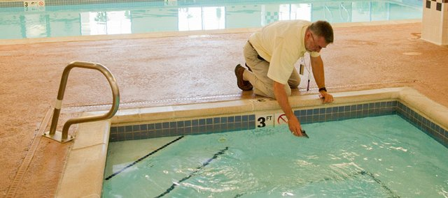 Jim McDaniel, environmental health specialist with the Douglas County Health Department, takes water samples during a recent inspection of the pool at the SpringHill Suites By Marriott at the Riverfront Plaza. Many pools in the area have had to spend thousands of dollars to comply with new federal safety regulations. Eudora leaders say the regulations may cause them to delay the opening of their city pool past Memorial Day.