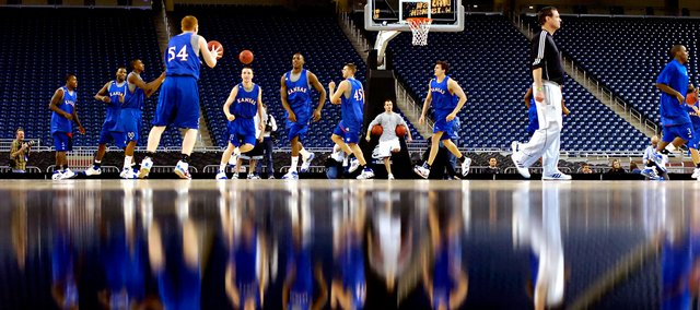 Reflected off a basketball court, the Kansas Jayhawks hold a practice. The team was practicing on a raised court with a dark painted border. By getting down at court level the photographer mirrored the action above and composed the frame equally divided between reflection and subject.