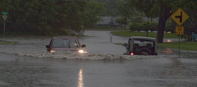 A driver fords the flooded intersection of 11th and Haskell Streets in front of the Public Works Department in east Lawrence as a Jeep sits submerged Friday, May 15, 2009.