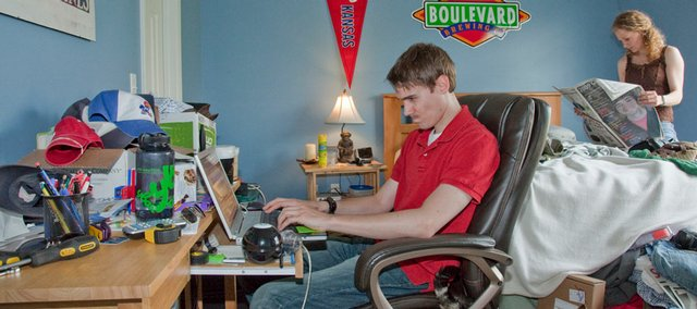 Dan Parker, a Kansas University senior who will graduate Sunday and a veteran of the U.S. Marine Corps, checks his e-mail at home while his girlfriend, Ruth Seeliger, reads the news and their cat prowls the room. Parker started a number of support services for military veterans during his time at KU.