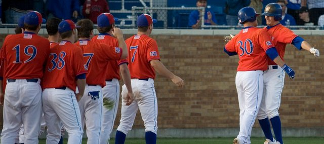 Kansas' Buck Afenir (30) chest-bumps Tony Thompson after a Thompson homerun during the game against Kansas State on Sunday, May 17, 2009, at Hoglund Ballpark.