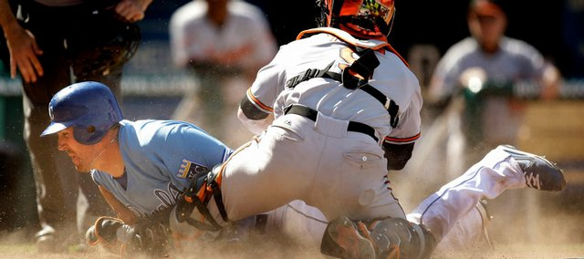 Kansas City's John Buck beats the tag by Baltimore catcher Gregg Zaun to score on a bunt single during the eighth inning. The Royals beat the Orioles, 7-4, Sunday in Kansas City, Mo.
