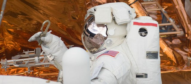 Astronaut John Grunsfeld attaches a tether during a spacewalk Saturday to perform work on the Hubble Space Telescope.