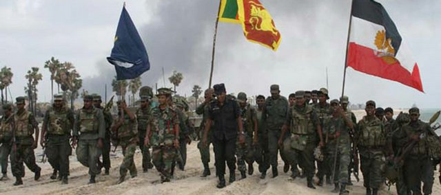 In this handout photograph provided by Sri Lanka's army dated Saturday, Sri Lankan soldiers carry their national flag, center, along with their unit flags at a site they say is the last stronghold of the Tamil Tiger rebels close to the war front in Kariyalamullivaikkal, Sri Lanka.