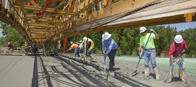 Contractors put the finishing touches on the first pour of concrete Monday for a new Kansas Turnpike bridge crossing the Kansas River. Monday's pour is the first of four base loads scheduled to form the deck for the bridge, which is part of a larger $130 million project to upgrade and overhaul portions of the turnpike as it passes through Lawrence.