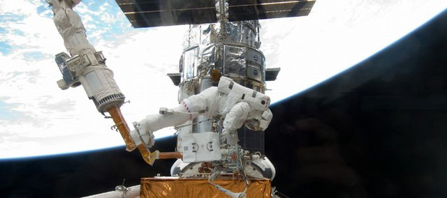 In this Sunday, May 17, photo released by NASA, astronaut Michael Good, positioned on a foot restraint on the end of Atlantis' remote manipulator system, works to refurbish and upgrade the Hubble Space Telescope. NASA has made its last service call on Hubble, and the telescope will eventually fall out of orbit and crash into the ocean.