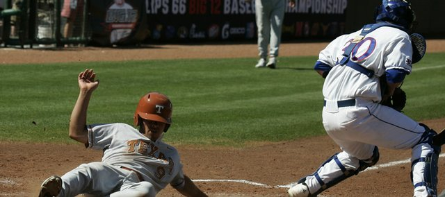 Texas' Michael Torres, left, slides safely home to score behind Kansas catcher Buck Afenir, right, in the fifth inning during a Big 12 baseball tournament game in Oklahoma City, Thursday, May 21, 2009. Texas won the game 9-3.