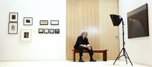 Lawrence Arts Center gallery and special programs director Rick Mitchell will be leaving his post after 15 years. Mitchell, pictured in the main gallery with paintings by Lawrence artists Stephen Johnson and Lisa Grossman, plans to focus on his own photography and writing