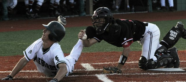 Above, Lawrence High catcher Jake Green, right, and Free State's Connor Stremel look to the home-plate umpire for his call on a close play at the plate on a suicide squeeze attempt. Stremel was called out on the play in the the third inning, and the Lions went on to a 2-1 victory over the Firebirds in a Class 6A regional Wednesday at FSHS. In top photo, LHS coach Brad Stoll, right, hugs Mitch Whitson.
