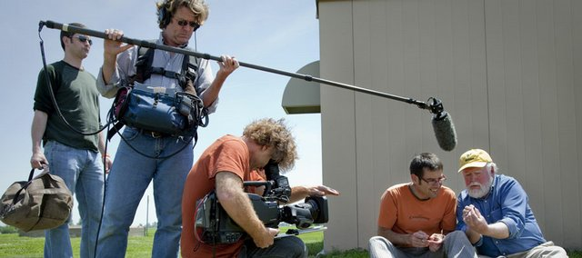National Geographic film crew members Charlie Miller, from left, Eddie O'Connor and Bob Poole grab footage as Martin Wikelski, associate professor of ecology and evolutionary biology at Princeton University, and Chip Taylor, director of Monarch Watch, attach a radio transmitter tag to a monarch butterfly Wednesday at the Lawrence Municipal Airport. National Geographic came along to film the tagging and tracking process for a segment on migrations.